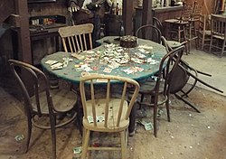Poker table at the Birdcage Theatre, with cards and money strewn on the tabletop and floor.