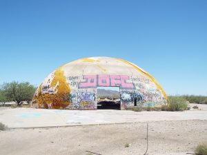 Abandoned concrete dome structure covered with graffiti