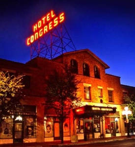 The front of the Hotel Congress at night, showing the iconic neon sign against a purple sky.