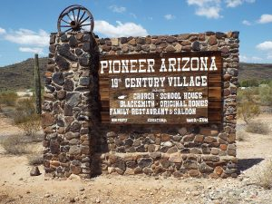 Old wooden sign pointing to Pioneer Village under a blue sky