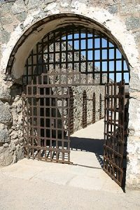 Iron front gates at Yuma Territorial Prison, with the gate slightly open.