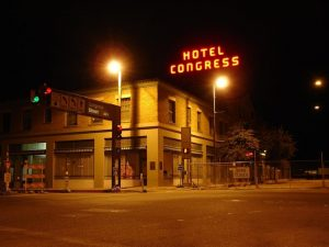 Hotel Congress at night viewed caddycorner, with the neon sign visible.