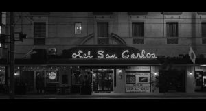 Black and white photo of the Hotel San Carlos, with flickering lights above the lobby entrance.