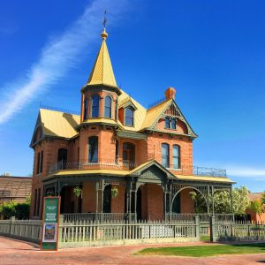 Front view of the Rosson House against a cloudy blue sky.