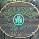 Wooden green sign that says Casey Moore's Oyster House at Ninth and Ash