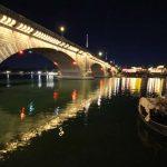 London Bridge at night illuminated by lights.